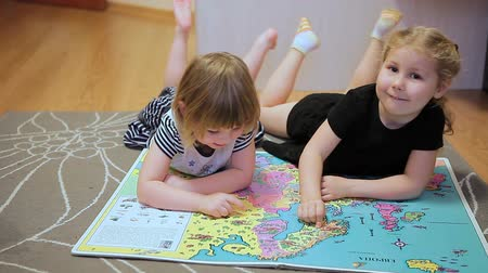 капелька : Two little girls with world map laying on the floor and showing different countries each other Стоковые видеозаписи