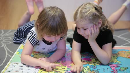 lefekvés : Two little girls with world map laying on the floor and showing different countries each other Stock mozgókép