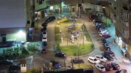 apartamentos : Vehicles parking in apartment building courtyard at evening, timelapse