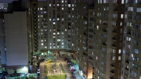 общественный : 4K, timelapse of residential high rise building at evening with illuminated windows and inner yard Стоковые видеозаписи