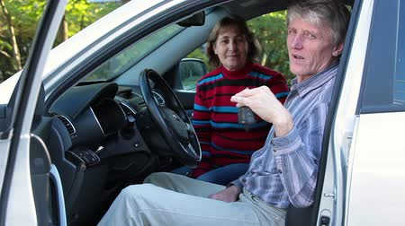new car : Senior man holding ignition keys in hand, sitting inside of new car with his wife