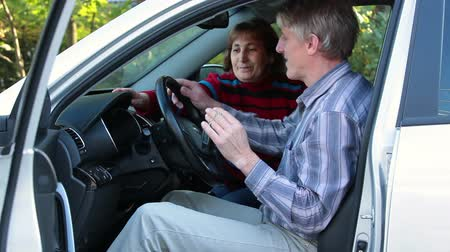 samochód : Senior couple sitting in new car with ignition keys