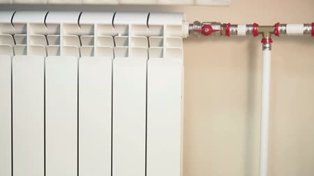 heating up metal : Camera lift down of white central heating convector with red valves on pipes, domestic room