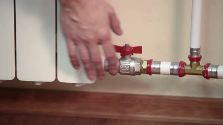 um objeto : Human hand touching hot radiator plates and turning off red valve on pipe