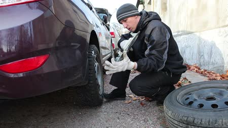 opravář : Man driver installing wheel with snow studded tyre and fixing plastic cover