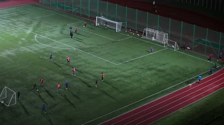 eğlence oyunları : Soccer evening training on stadium, teenagers playing game on the green field, winter season
