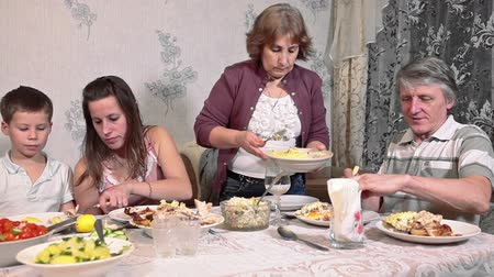 vacsora : Elderly mother arranges food on plates for family members, evening dinner