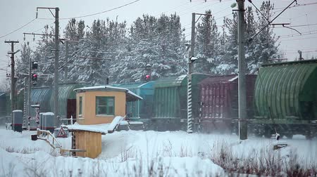 lokomotif : Freight train passing railroad crossing at winter season, railway booth Stok Video