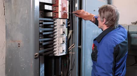 technikus : Electrician in uniform is on work, electric panel with switches