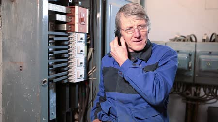 elektryk : Senior electrician worker in glasses talking with cellphone in high voltage room