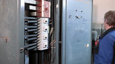 elektryk : High voltage electric control panel with switches and electrician worker inspecting and checking