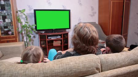 assistindo : Mother with two children a son and a daughter watching green screen tv, when sitting on sofa