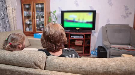arka görünüm : Caucasian mature mother with young daughter watching cartoons on tv in living room