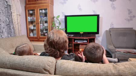 radość : Mother with two children watching tv show on green screen in living room