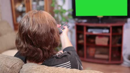 tv screen : Mature woman changing channels with the TV remote on television panel with green screen Stock Footage