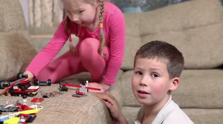 enjoyment : Young brother and sister playing with constructor bricks on sofa Stock Footage