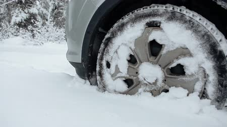 sıkışmış : Suv with snowy wheels and winter tires driving on snow, cloae-up view Stok Video