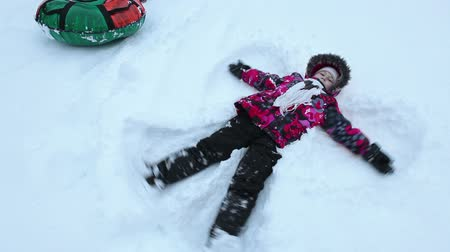 snow angel : Caucasian young girl makes snow angel lying on back,  winter season.