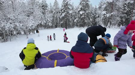 csőrendszer : Russian children are preparing to descend from the mountains to the tubing in the winter. Karelia, northern Russia Stock mozgókép