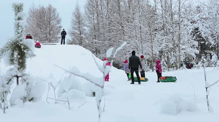 sporty zimowe : Downhill slope in snowy winter forest with families riding with tubes from top. Northern Karelia, Russia