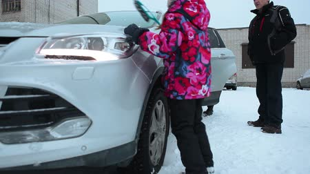 winter place : Family preparing car at winter season, brushing snow and heating engine on parking place