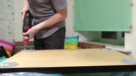 kitchen furniture : Worker holding electic drill in hands while installing table legs at home, foreground focus