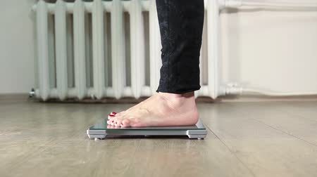 com escamas : Human legs standing on weight scale in clear domestic room Stock Footage