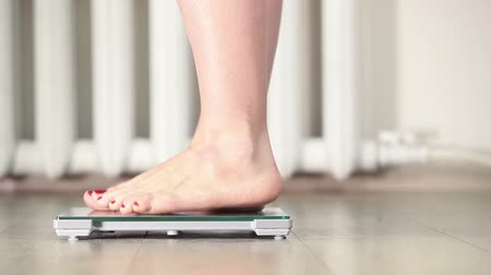 com escamas : Human barefoot legs stepping on floor scales for weighing, camera moving