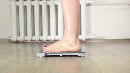 com escamas : Women barefoot legs stepping on floor scales for weighting