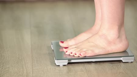 com escamas : Human feet standing on scales and wiggling her toes, close-up view
