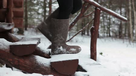 fur boots : Woman going down the timber stairs in felt boots, winter season. Camera moving