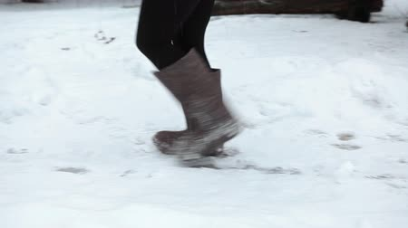 bota : Woman walk on the snow in felt boots, side view, winter season in Russia