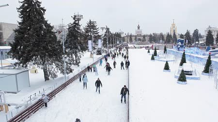 korcsolya : MOSCOW, RUSSIA - CIRCA JAN, 2015: People are on skating rink in Moscow VDNKh area, near the central pavilion building. VDNKh is the all-Russian Exhibition Center with huge skating ring at winter season Stock mozgókép
