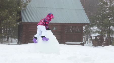 kardan adam : Playful child climbing on huge snowball at rural timber house yard at winter season
