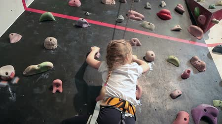wspinaczka : Little girl with assistance rope falling down from climbing wall while bouldering
