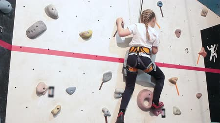 wspinaczka : Little girl has workout of rock-climbing in sport gym, climbing the wall