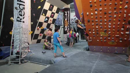sertlik : SAINT-PETERSBURG, RUSSIA - CIRCA FEB, 2015: Rock-climbing championship is in IgelsClub. Sportsmen climb the walls. Igelsclub is a parkour park with climbing gym and trampolines