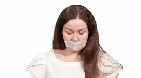 cisza : Woman with tape on her mouth plaintively looking at camera, white isolated background