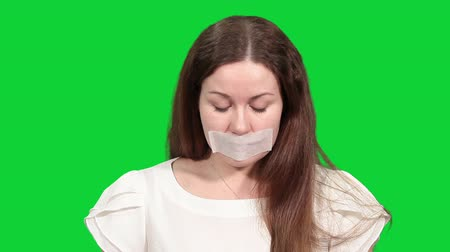 лента : Woman with tape on her mouth plaintively looking at camera, green screen chromakey background Стоковые видеозаписи