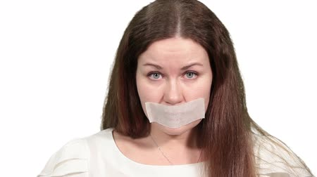 gag : Sad woman with tape on mouth heavy breathing and plaintively looking at camera, white isolated background Stock Footage