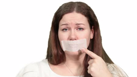 gag : Sad Caucasian woman pointing at tape on the mouth, speechless man, white isolated background Stock Footage