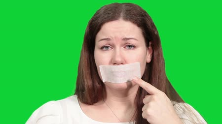 gag : Sad Caucasian woman pointing at tape on the mouth, speechless man, green screen chromakey background Stock Footage