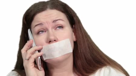 incapacidade : Woman with sealed mouth trying to talk on the cellphone, isolated white background
