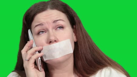 incapacidade : Woman with glued mouth has impossibility to speak by cellphone, greenscreen chromakey background, isolated