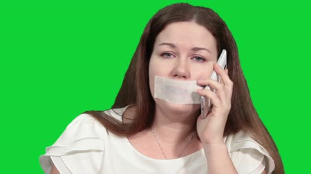 incapacidade : Beautiful woman shaking his head with gag on her mouth when can not to speak on the mobile phone, green chroma key background