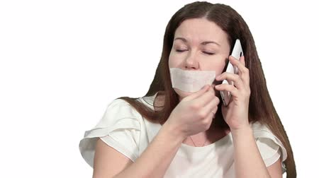 incapacidade : Caucasian woman talker removing the gag from her mouth and speaking on the phone, isolated on white background Stock Footage