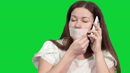 incapacidade : Caucasian woman talker removing the gag from her mouth and speaking on the phone, green chroma key background Stock Footage