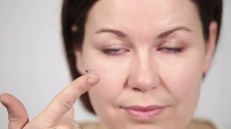 soczewki kontaktowe : Caucasian woman holding eye lens on finger, camera focusing on face and hand Wideo