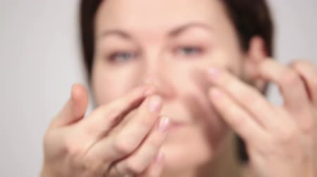 kontakt : Young woman holding and inserting daily contact lens in eye Wideo