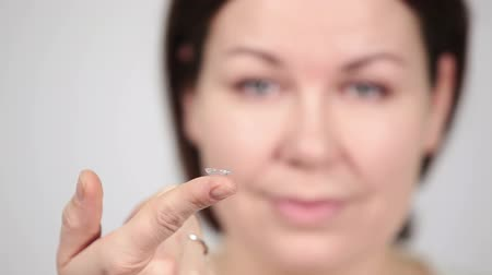 kontakt : Caucasian woman holding extended wear contact lens on finger, camera focusing on hand